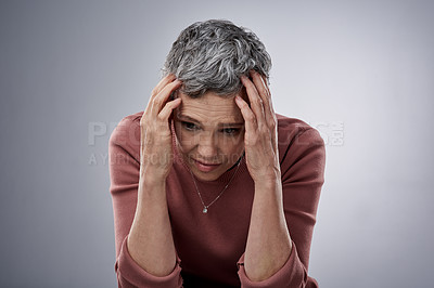 Buy stock photo Studio shot of a mature woman looking stressed out against a gray background