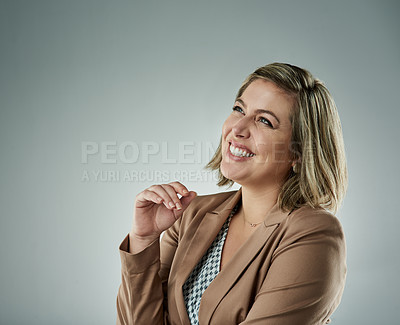Buy stock photo Studio shot of a happy young businesswoman looking thoughtful against a gray background