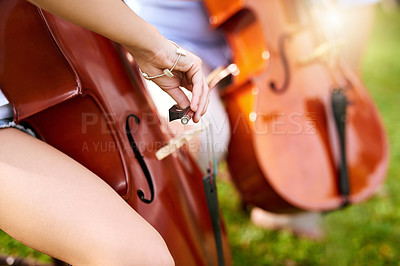 Buy stock photo Closeup of two unrecognizable people playing classical string instruments together in the backyard of their home during the day