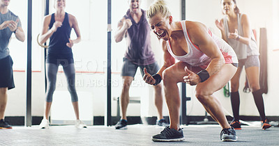 Buy stock photo Shot of a group of young people standing in a circle at the gym and motivating each other