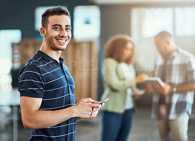Buy stock photo Portrait of a young designer using a cellphone in an office