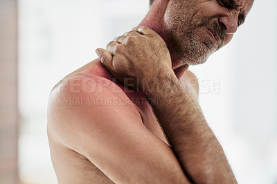 Buy stock photo Shot of a uncomfortable looking shirtless middle aged man holding his shoulders due to pain while being seated on the floor of a fitness studio