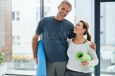 Buy stock photo Portrait of a cheerful middle aged couple standing together with their exercise mats after doing yoga inside of a fitness studio