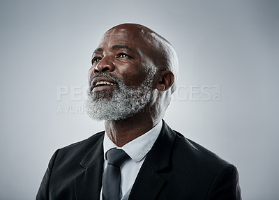 Buy stock photo Studio shot of a mature businessman looking up against a grey background