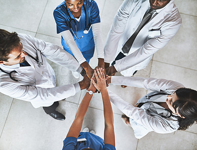 Buy stock photo High angle shot of a diverse team of doctors joining their hands together in a hospital