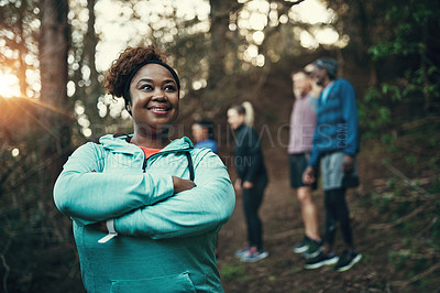 Buy stock photo Cropped shot of a sporty young woman ready to workout while waiting for her friends in the background in the forest