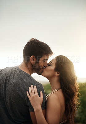Buy stock photo Rearview shot of a young couple kissing at the beach