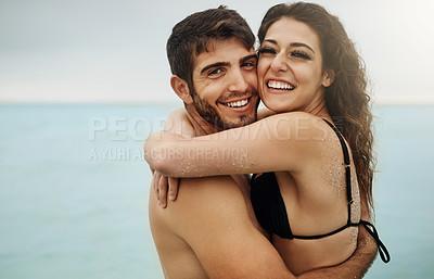 Buy stock photo Shot of a young couple enjoying a beach getaway