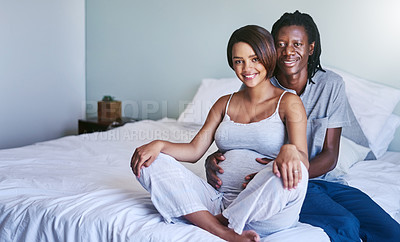 Buy stock photo Shot of a young expecting couple sitting on their bed