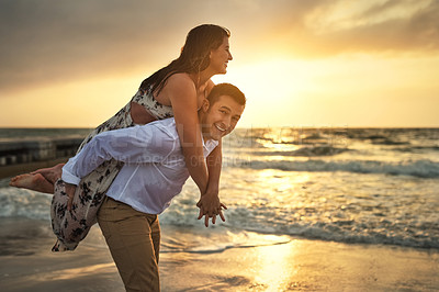 Buy stock photo Cropped portrait of a handsome young man piggybacking his girlfriend on the beach