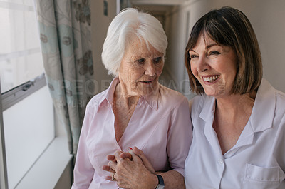 Buy stock photo Shot of a senior woman and a nurse going for a walk in a retirement home
