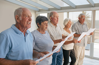 Buy stock photo Shot of a group of senior people singing from sheets together in a retirement home
