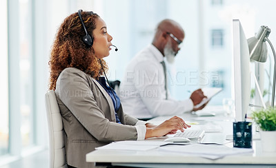 Buy stock photo Cropped shot of an attractive young female call center agent working in the office alongside a male coworker