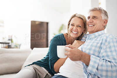 Buy stock photo Cropped shot of an affectionate mature couple relaxing together on the sofa at home