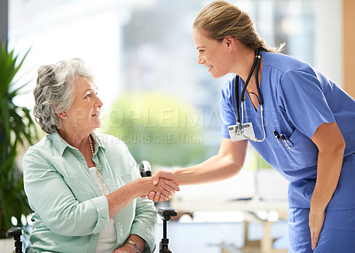 Buy stock photo Cropped shot of an attractive female nurse shaking hands with her wheel-bound senior patient in the hospital