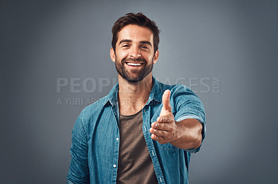 Buy stock photo Studio portrait of a handsome young man extending his arm for a handshake against a grey background