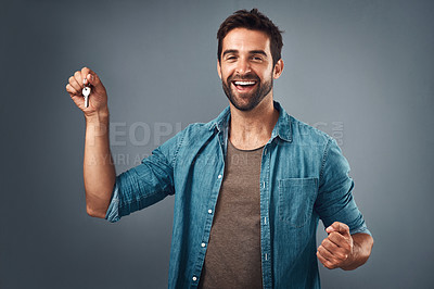 Buy stock photo Studio shot of a handsome young man holding a set of keys against a grey background