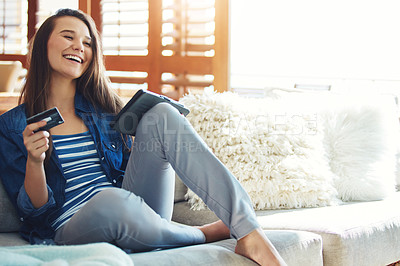 Buy stock photo Shot of an attractive young woman using her tablet to shop online while relaxing on the sofa at home