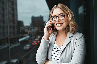 Buy stock photo Shot of a young businesswoman talking on a cellphone on the office balcony
