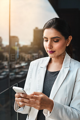 Buy stock photo Shot of a young businesswoman using her cellphone on the office balcony