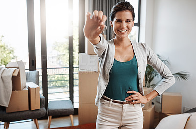 Buy stock photo Cropped portrait of an attractive young woman holding the key to her new home while moving in