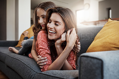 Buy stock photo Full length shot of an attractive young woman and her daughter hugging while spending time together at home