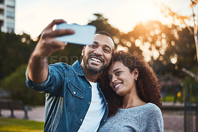 Buy stock photo Shot of a young couple taking selfies together outdoors