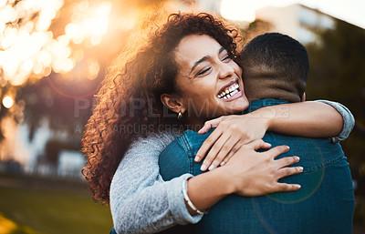 Buy stock photo Shot of a young woman hugging her boyfriend outdoors