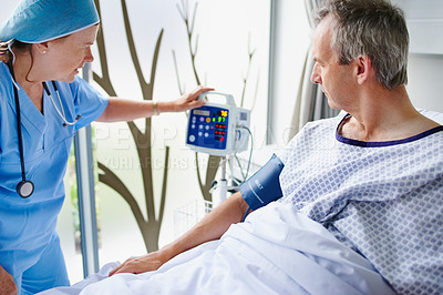 Buy stock photo Cropped shot of a mature female doctor tending to a male patient in his hospital bed