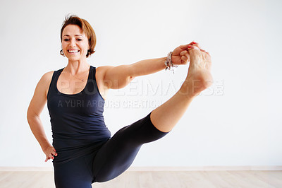 Buy stock photo Portrait of a focused young woman practicing yoga poses inside of a studio during the day