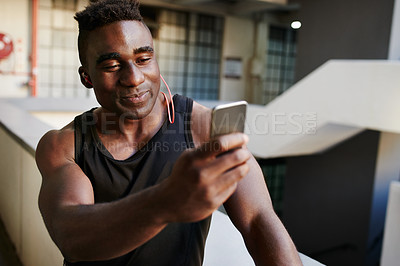 Buy stock photo Shot of a sporty young man taking selfies with a cellphone during his workout out in an urban apartment block