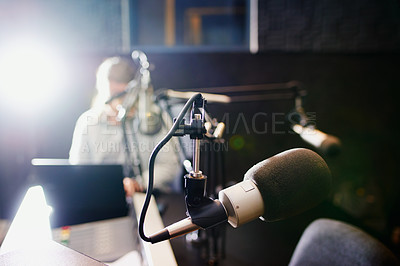 Buy stock photo Shot of a microphone in a recording studio with the presenter blurred in the background