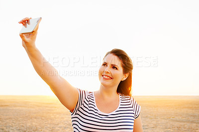 Buy stock photo Cropped shot of a beautiful young woman taking a selfie while spending the day on the promenade at the beach