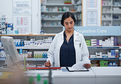 Buy stock photo Shot of a mature pharmacist working on a computer in a chemist