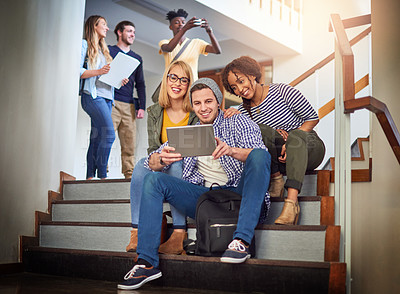 Buy stock photo Shot of a group of university students using a digital tablet on the staircase at campus