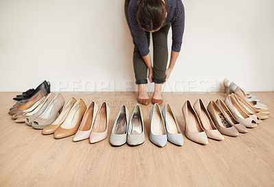 Buy stock photo Cropped shot of an unrecognizable young woman trying on a selection of high heels