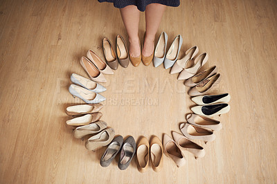Buy stock photo Cropped shot of an unrecognizable woman standing on a wooden floor surrounded by high heels