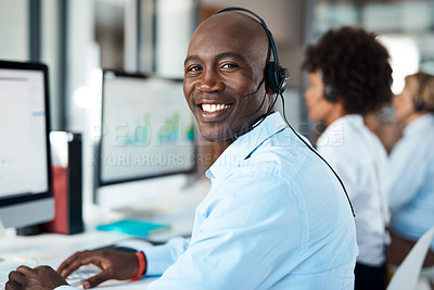 Buy stock photo Portrait of a young call centre agent working alongside his colleagues in an office