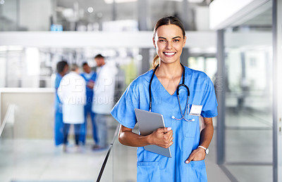 Buy stock photo Portrait of a young doctor holding a digital tablet in a hospital with her colleagues in the background