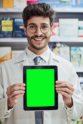 Buy stock photo Cropped portrait of a handsome young male pharmacist holding up a tablet while working in a pharmacy