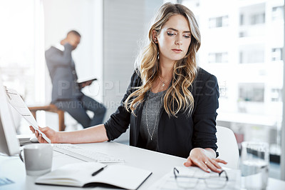 Buy stock photo Shot of a young businesswoman using a computer and writing notes at her desk in a modern office