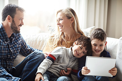 Buy stock photo Shot of two adorable brothers using a digital tablet together with their parents on the sofa at home
