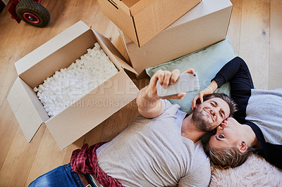 Buy stock photo High angle shot of a happy young couple taking a selfie in their new home