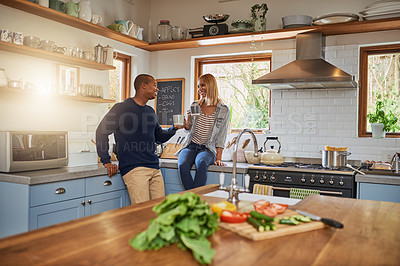 Buy stock photo Shot of a young couple talking while having coffee at home