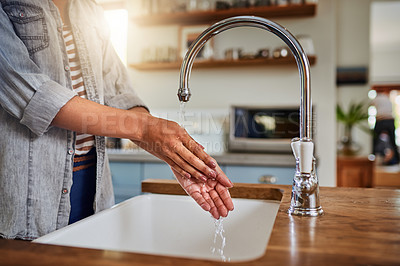 Buy stock photo Shot of an unrecognizable woman washing her hands in the kitchen sink