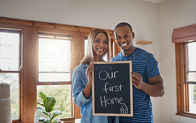 Buy stock photo Shot of a couple holding up a blackboard as they move into their new house