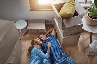 Buy stock photo Shot of a couple lying on the floor with boxes surrounding them in their new house