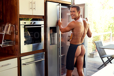 Buy stock photo Cropped shot of a handsome young shirtless man getting items from the refrigerator at home