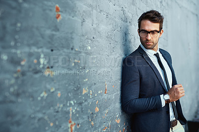 Buy stock photo Cropped shot of a handsome young businessman standing against a grey facebrick wall