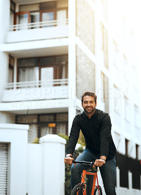 Buy stock photo Cropped portrait of a handsome young man traveling through the city by bike